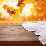 Autumn leaves background. Empty wooden deck table with tablecloth. - 228669625