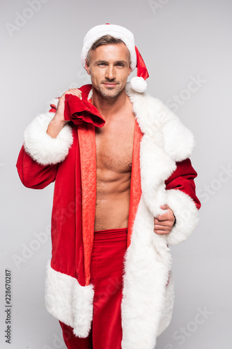 Leinwandbild Motiv handsome man in santa costume holding bag with presents and looking at camera isolated on grey