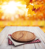 Autumn landscape and pizza board with napkin on wooden table. Top view mock up - 228673408
