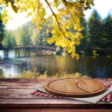 Pizza boapd and napkin on table over blurred trees and river as background, product display template. Selective focus. - 228673689