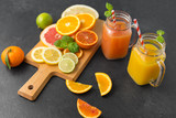 food , healthy eating and vegetarian concept - mason jar glass with juice and citrus fruits on slate table top