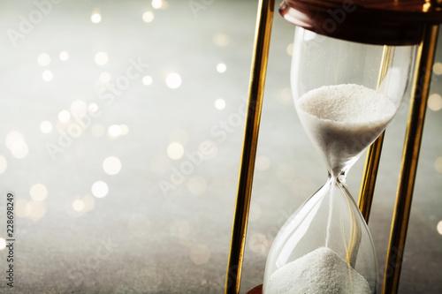 Leinwanddruck Bild Sand running through the hourglass. Time keeper concept. Boke effect.