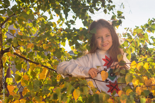Cute girl with flowing hair in nature. A girl stands in the branches of a birch. © Natallia