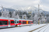 Regionalzug in verschneitem Bahnhof
