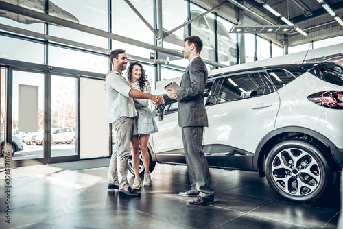 Leinwandbild Motiv Young couple shaking hands with sales agent after a successful car buying
