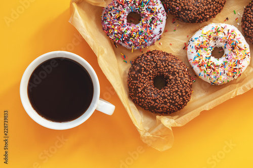Wall mural Delicious glazed donuts in box and cup of coffee on yellow surface. Flat lay minimalist food art background. Top view.