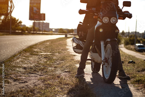 Close view on the legs of a motorcyclist on the motorcycle on an empty road at sunny day