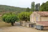 zijkant van boerderij in de Provence met schuren, woonhuis, oprijlaan en vuilnisbakken