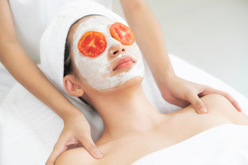 Woman get facial mask with tomato cream extract. © Blue Planet Studio