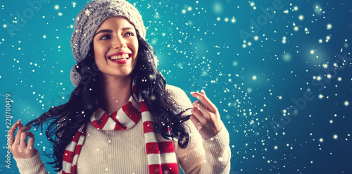 Happy young woman in winter clothes in a snowy night