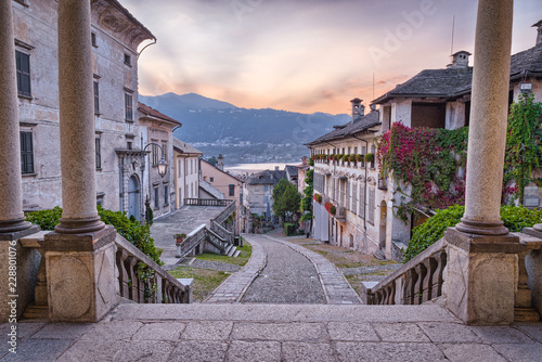 Beautiful scenic alley with historic and traditional houses and cobbled street at sunset. Picturesque Italian village, Orta San Giulio (street Albertoletti), on lake Orta, north Italy