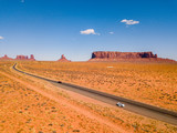 July 30, 2018. Monument Valley National Park, Utah, USA. White Ford Mustang parked by the side of the road at Monument Valley National Park with an amazing view on the infinite road through the desert