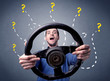 Leinwanddruck Bild - Young man holding black steering wheel with question marks around him
