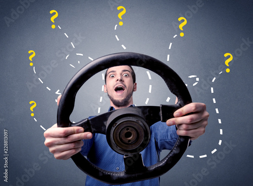Leinwanddruck Bild Young man holding black steering wheel with question marks around him