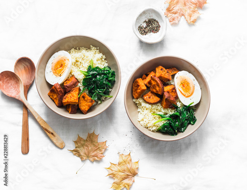 Sweet potato, couscous, spinach, egg buddha bowl on light background, top view. Vegetarian food concept - 228813629