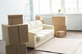 Relocation, new home and real estate concept - Moving boxes and sofa in empty room - 228816607