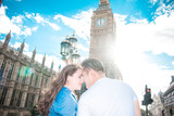 Happy couple by Big Ben, River Thames, London, England, United Kingdom. Romantic young couple loving each other during travel. Blue sky.
