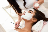 Aesthetics applying a mask to the face of a beautiful woman - 228833693