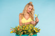 Floristics, holidays, flower shop and people concept - Beautiful blond young woman fixing bouquet of tulips on blue background.