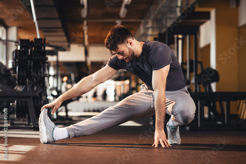 Sticker Handsome man doing warm up in the gym and stretch legs