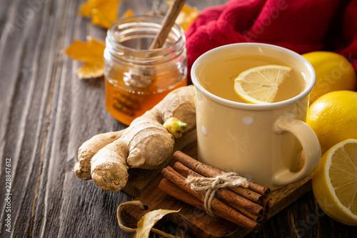 Autumn hot drink - ginger, lemon, honey tea and ingredients, wood back - 228847612