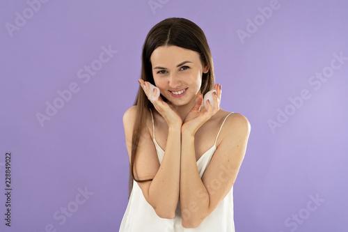 Leinwanddruck Bild portrait beautiful young woman washing face with foam