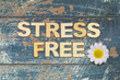 Quadro Stress free written with wooden letters on rustic wooden surface and white daisy flower
