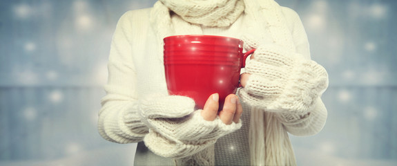 Woman holding a cup of coffee on a shiny light background © Tierney