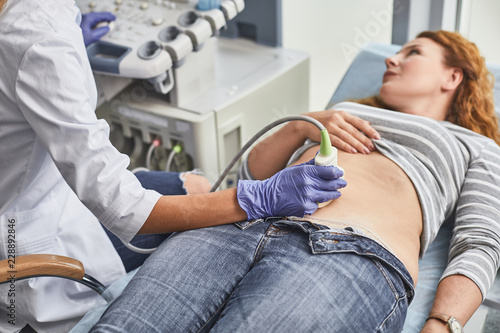 Leinwanddruck Bild Expecting pregnancy. Doctor in white lab coat and sterile gloves examining red-haired woman with ultrasound scanner