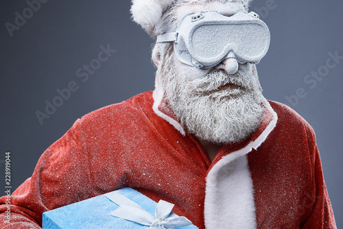 Leinwanddruck Bild Studio portrait of bearded old man in Santa costume covered with snow. He is holding blue gift box with ribbon