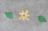 The textures of ceramic flower and leaf on ground.