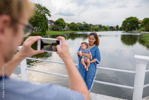 Fototapeta Multi-ethnic young family bonding together at the park