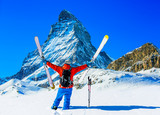 Man skiing on fresh powder snow. Ski in winter season, mountains and ski touring backcountry equipments on the top of snowy mountains in sunny day with Matterhorn in background, Zermatt in Swiss Alps. - 228943465