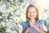 Happy little girl playing in spring cherry garden - 228979255