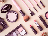 top view of cosmetics concept with lipstick, makeup products, Eyeshadow Palette, powder on cream color table background. - 228980409