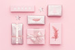 Gift wrapping. Pink nordic christmas gifts isolated on pastel pink background. Wrapped xmas boxes.