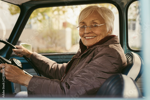 Foto Murales Senior woman driving a car on winter day