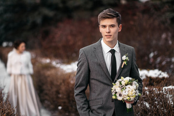 Handsome young man with bouquet in hands in winter park. His bride is standing on a blurred background. Wedding day