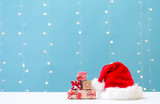 Santa hat with small gift boxes on a shiny light blue background - 228998882