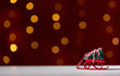 Toy slide carrying a Christmas tree on a shiny light dark red background