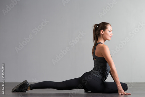 athletic fitness young woman doing sports exercises on a gray background - 229000226