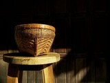 the old bamboo basket on wooden chair with sunlight on surface and blur old wooden wall background in vintage style, Thai  art of craft concept