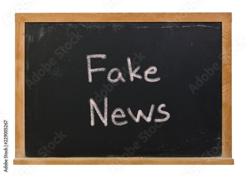 Fake news written in white chalk on a black chalkboard isolated on