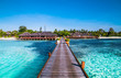 Tropical travel destinations with Maldives island and wooden wharf