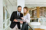 Young businesswoman and businessman look on digital tablet and discuss aout project - 229026481