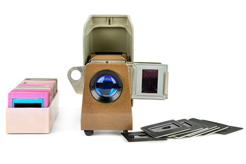 Old slide projector and set of slides isolated on white background.
