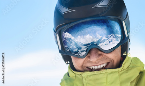 fototapeta na ścianę Close up of the ski goggles of a man with the reflection of snowed mountains. A mountain range reflected in the ski mask. Man on the background blue sky. Wearing ski glasses. Winter Sports.