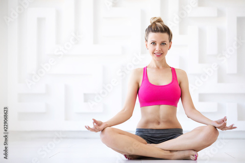 Beautiful smiling woman in lotus position. Yoga.