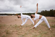 Leinwanddruck Bild - People, fitness, sport, friendship, family and lifestyle concept. Professional female yoga instructor and her teenage son both in white clothes, standing barefooted on sand, doing Utthita Trikonasana