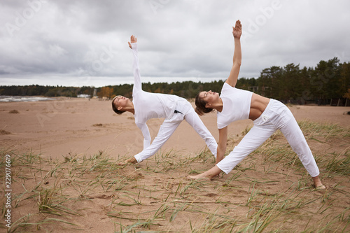 Leinwanddruck Bild People, fitness, sport, friendship, family and lifestyle concept. Professional female yoga instructor and her teenage son both in white clothes, standing barefooted on sand, doing Utthita Trikonasana